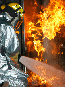 Firefighter extinguishes a simulated structural fire.の写真素材 [FYI02104852]