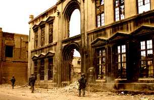 Soldiers patrolling past the facade of a demolished buildingの写真素材 [FYI02105037]