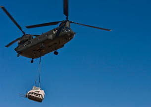 A U.S. Army CH-47 Chinook carries a bulldozer to a drop siteの写真素材 [FYI02105122]