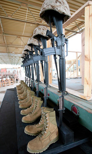 Boots, rifles, dog tags, and protective helmets stand in solの写真素材 [FYI02105186]