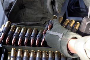 A soldier reaches for a belt of .50 caliber ammunition.の写真素材 [FYI02105427]