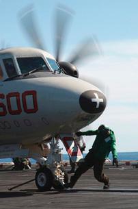 A flight deck crew member performs final checks on an E-2C Hの写真素材 [FYI02105749]