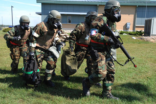 Soldiers dressed in chemical warfare gear carry equipment.の写真素材 [FYI02105924]