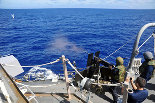 A Sailor fires a .50 caliber machine gun aboard USS McCampbell.の写真素材 [FYI02106025]
