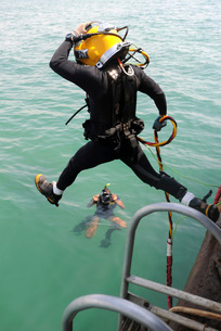 A photographer documents a Navy diver as he enters the water.の写真素材 [FYI02106097]