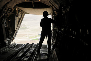 A loadmaster watches supplies airdrop out of the C-27J Spartan.の写真素材 [FYI02106102]