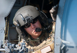 A U.S. Air Force Airman peers out the side of a HH-60 Pave Hawk.の写真素材 [FYI02106134]