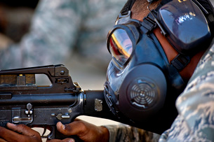 Air Force Basic Military Training trainee fires at his target while wearing his gas mask.の写真素材 [FYI02106159]