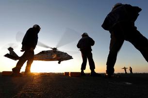 Sailors watch a helicopter lift off the flight deck of USS Bonhomme Richard.の写真素材 [FYI02106167]