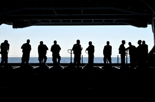 Silhouette of sailors standing in the hangar bay aboard USS Carl Vinson.の写真素材 [FYI02106240]