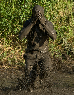 A participant wipes mud from his face after jumping in a pond.の写真素材 [FYI02106247]