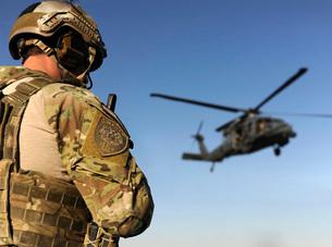A pararescueman awaits the landing of an HH-60 Pave Hawk.の写真素材 [FYI02106248]