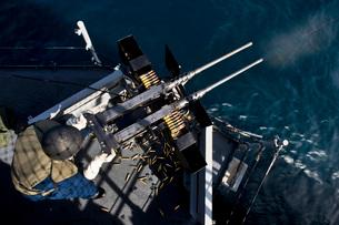 Seaman fires twin .50 caliber machine guns aboard USS Boxer.の写真素材 [FYI02106259]