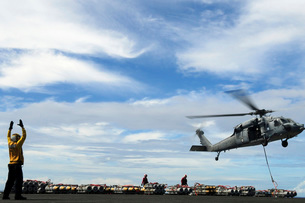 An MH-60S Sea Hawk lifts a pallet of ordnance from the aircraft carrier USS Ronald Reaganの写真素材 [FYI02106340]
