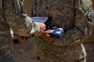 A soldier is presented the American Flag and certificate during a ceremony.の写真素材 [FYI02106378]
