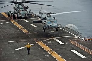 An MH-60S Sea Hawk lands aboard the amphibious assault ship USS Makin Island.の写真素材 [FYI02106604]