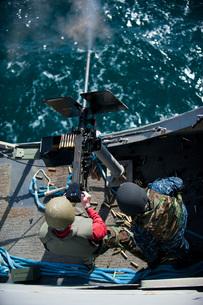A sailor fires a .50-caliber machine gun aboard USS New Orleans.の写真素材 [FYI02106605]