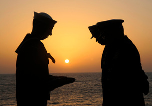 Airman presents commanding officer with an American flag during a burial at sea.の写真素材 [FYI02106626]
