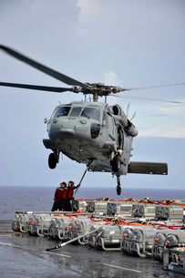 Sailors hook an ammunition pallet to an MH-60S Sea Hawk helicopter.の写真素材 [FYI02106686]