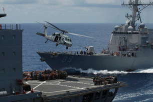 An MH-60S Knighthawk helicopter transports a pallet of supplies to USS Essex.の写真素材 [FYI02106723]