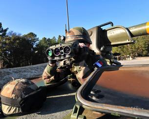 A soldier scans the horizon through a pair of binoculars.の写真素材 [FYI02106740]