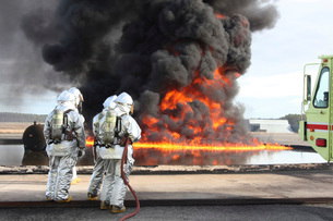 Firefighting Marines watch as a training fire builds intensity.の写真素材 [FYI02106859]