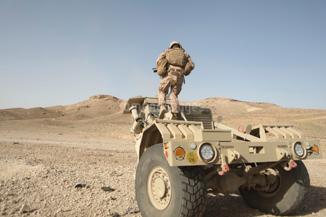 Soldier climbs a damaged Husky Tactical Support Vehicle.の写真素材 [FYI02106924]