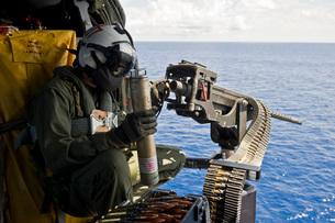 Naval Aircrewman manning a .50 caliber machine gun aboard a MH-60 Seahawk.の写真素材 [FYI02106972]