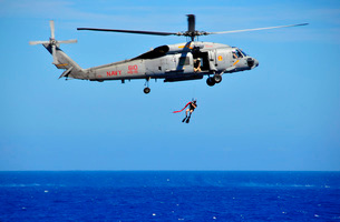 A search and rescue swimmer is lowered from an SH-60F Sea Hawk helicopter.の写真素材 [FYI02107009]