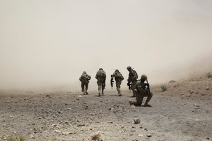 U.S. Army Captain provides security for his escorts as they run through a dust cloud.の写真素材 [FYI02107037]