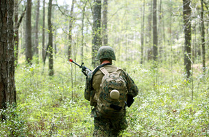 A U.S. Marine patrols through a forest during a field exercise.の写真素材 [FYI02107103]