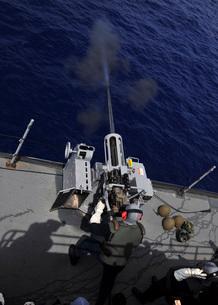 Gunner fires a Mark 38 machine gun aboard USS Frank Cable.の写真素材 [FYI02107207]