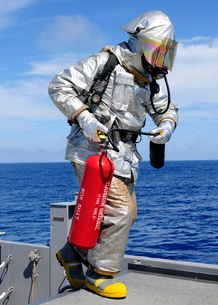 Firefighter carries a CO2 fire extinguisher onto the flight deck of USS Denver.の写真素材 [FYI02107303]