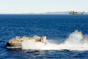An SH-60F Seahawk helicopter follows a Landing Craft Air Cushiion in the Coral Sea.の写真素材 [FYI02107332]