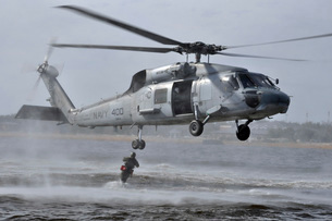 A search and rescue swimmer jumps from an SH-60F Sea Hawk helicopter.の写真素材 [FYI02107348]