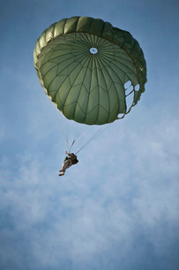 An Airman descends through the sky with parachute deployed.の写真素材 [FYI02107473]