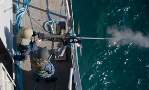 A sailor fires a .50-caliber machine gun aboard USS New Orleans.の写真素材 [FYI02107549]