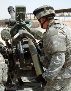 U.S. Army Soldier loads a 105mm artillery round into a M119 Howitzer.の写真素材 [FYI02107604]