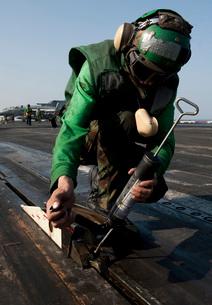 Airman greases the catapult shuttle on USS John C. Stennis.の写真素材 [FYI02107689]