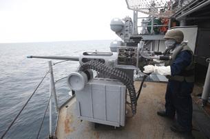 A gunner mans a Mk-38 machine gun aboard USS Kearsarge.の写真素材 [FYI02107858]