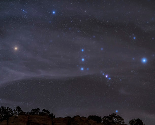 The Orion constellation rises over a hill through high thin clouds.の写真素材 [FYI02108258]