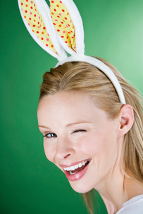 A young blonde woman wearing rabbit ears, winkingの写真素材 [FYI02108327]