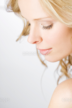A portrait of a young blonde woman looking down, close-upの写真素材 [FYI02108332]