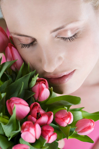 A young woman holding a bunch of pink tulips, close-upの写真素材 [FYI02108360]