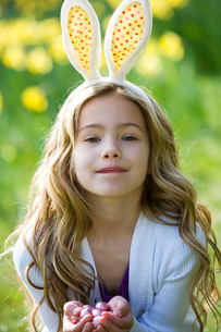 A young girl holding Easter eggs, wearing bunny earsの写真素材 [FYI02108587]