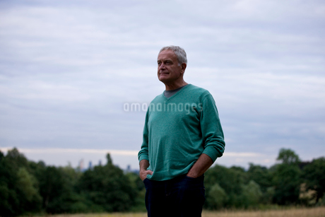 A senior man standing in a field, looking thoughtfulの写真素材 [FYI02108609]