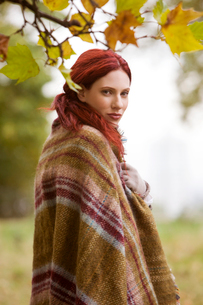 A young woman standing outdoors, wrapped in a blanketの写真素材 [FYI02108615]