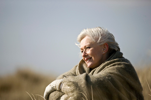 A senior woman sitting amongst the sand dunes, wrapped in aの写真素材 [FYI02108795]