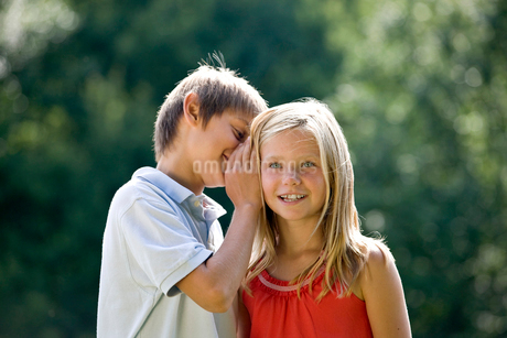 A young boy whispering to a young girlの写真素材 [FYI02108897]