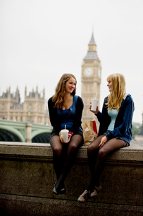 Two teenage girls sitting near Big Ben, having lunchの写真素材 [FYI02109317]